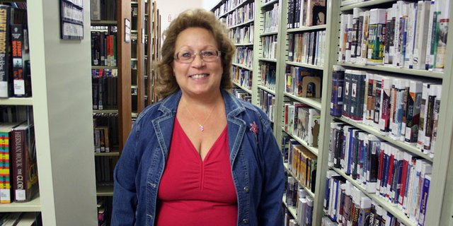 Charleah Firestone, a library assistant at the Craig branch of the Moffat County Library, pauses between a row of bookshelves. A retired music teacher, Firestone will be holding a harp concert in early December at the library featuring Celtic and Christmas music.