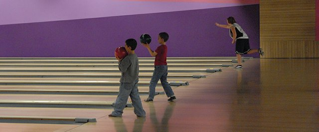 Two boys from the bantam (ages 7-13) league at Thunder Rolls Bowling Center prepare to bowl Sunday evening, while a high-roller (ages 14-18) bowls in the background. Many of the newer participants in youth leagues bowl without an approach so they can initially focus on their arm technique