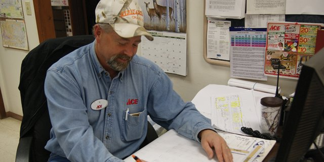 Ty Stewart sits at his desk working at the MJK Sales and Feed located on Ranney Street. Stewart is helping to convert the older location into a building and design center targeted towards contractor and commercial customers.