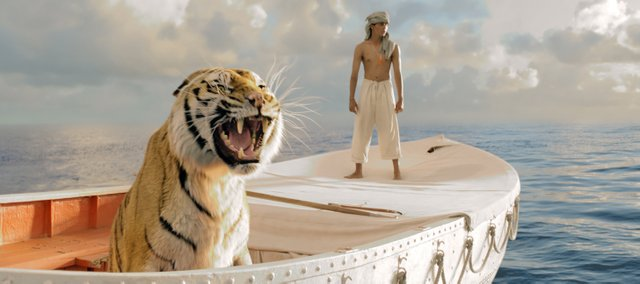 "Pi Patel (Suraj Sharma) and his feline traveling companion Richard Parker survey the emptiness of the ocean in ""Life of Pi."" The movie is about an Indian teenager who survives a shipwreck and must live for weeks alone on a lifeboat with an adult Bengal tiger."
