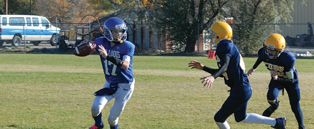 Cole White looks to pass the ball during a Craig Middle School football game vs. Rifle in September. White, a seventh-grader at CMS, along with his fourth-grade brother Seth, was invited to play at the Offense-Defense Football Camp Youth All-American Bowl starting Dec. 26 in Houston.