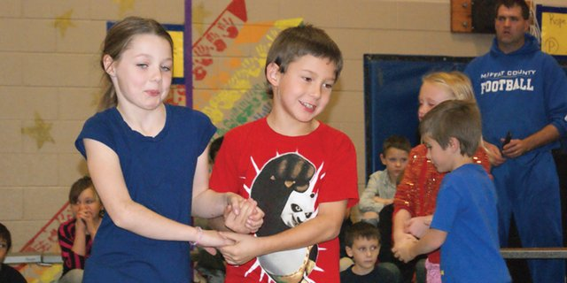 Ridgeview Elementary School second graders, Malia Graham, left, and Kyton Rodriguez, perform a line dance during their school concert Thursday afternoon.