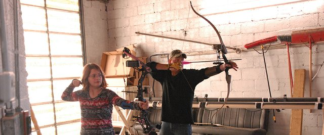 Winter Rogers (left), 10, and her father Bob take aim and shoot from the 20-yard line on the archery lanes at InsideOut Sports, 561 Russell St., during the business&#39; grand opening Saturday. InsideOut offers baseball and softball batting cages as well as the archery lanes indoors.