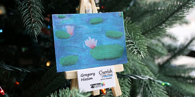 An easel ornament displaying artwork by kids from the Cherish the Little Things art show hangs on the Connections 4 Kids Christmas tree at the Festival of Trees. Connections 4 Kids tree won out of 23 trees and was awarded $500 to use towards its programs. 