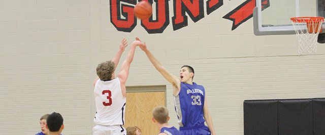 Freshman Javen Gumber contests the shot of a Gunnison player during Saturday's game in Gunnison. The Bulldogs defense stifled the Cowboys en route to a 61-51 win.