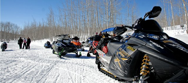 Sleds sit idle as their riders stop at the first station during last Saturday's 11th annual Poker Run. The event, hosted by the Northwest Colorado Snowmobile Club, raises fund for the club's scholarship program.