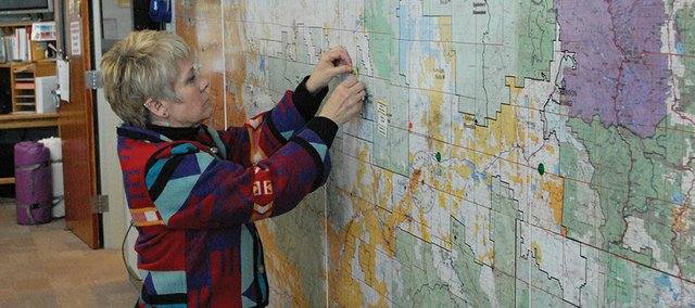 Lynn Barclay looks over the map in the dispatch center at the Bureau of Land Management Little Snake Field Office, where she works. Barclay is a BLM Mitigation/Education/Prevention Specialist.