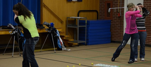 Brittany Corey (left) and Shianna Dockins work on their chipping in the gym at East Elementary School. The girls golf team from Moffat County High School has to practice indoors until the snow melts and conditions improve for golfing outside, like many of the outdoor spring sports in Craig.
