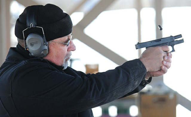 Gun owner Bob Reese fires his Glock .45-caliber pistol at the Routt County Rifle Club on Tuesday afternoon. Routt and Moffat county sheriffs said they will not enforce gun-control measures expected to be signed by Gov. John Hickenlooper today.
