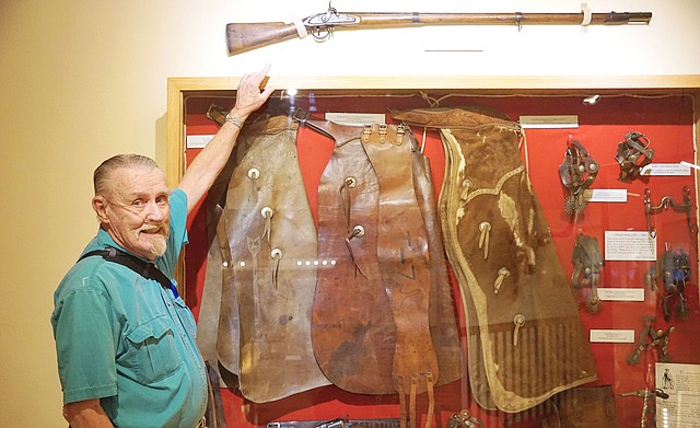 A Harper's Ferry 1795 Musket, after serving in at least one western battle, is on display at the Museum of Northwest Colorado. Bill Mackin, museum volunteer and founder of the Cowboy and Gun Fighter Collection, stands below the gun.