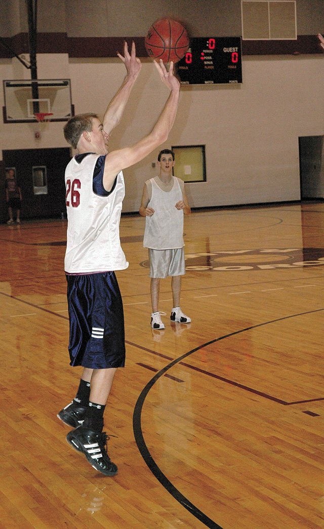 Freshman Cody Miles attempts a 3-point shot during a transition offense drill at Tuesday's Soroco varsity basketball practice as senior guard David Roberts watches.