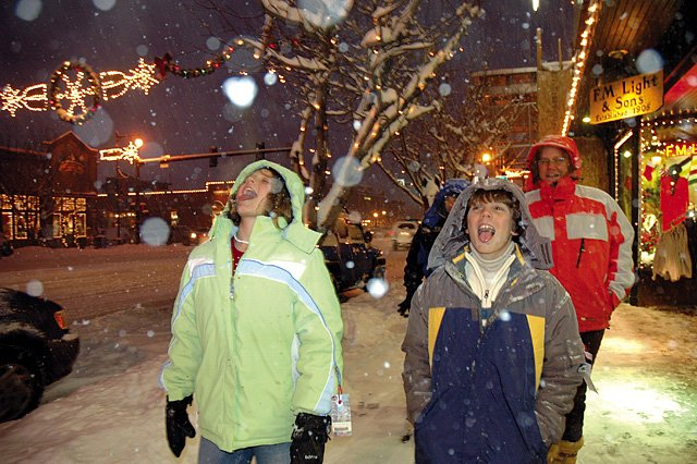 Cristina Pimenta, left, and her brother Bito catch snowflakes while shopping downtown with their parents, Bito Sr. and Melissa, on Wednesday. The afternoon snowfall was a gift for skiers but a nightmare for travelers trying to make it to the Yampa Valley from Denver.