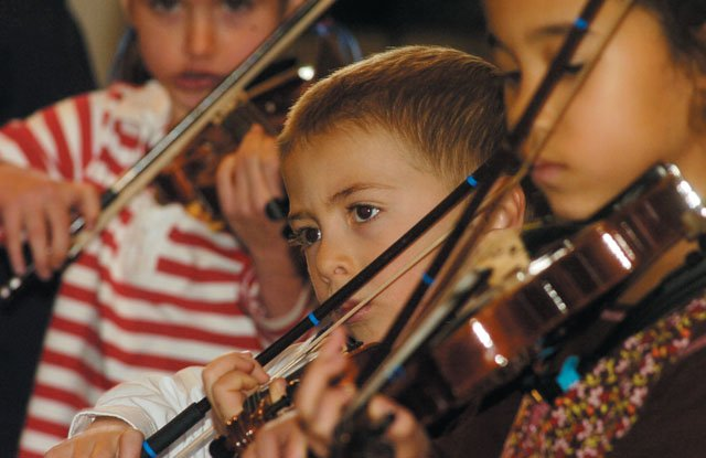 First-grader Jacob VanDerWerf concentrates on his notes during the Strings in Concert performance at the Lowell Whiteman Primary School on Friday afternoon.