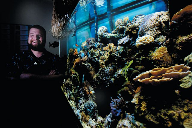 Gavin Graham stands in front of his 210-gallon fish tank in the relaxation reef room at Tropical Rockies in Steamboat Springs.  The tank is home to a self-sustaining coral reef ecosystem.