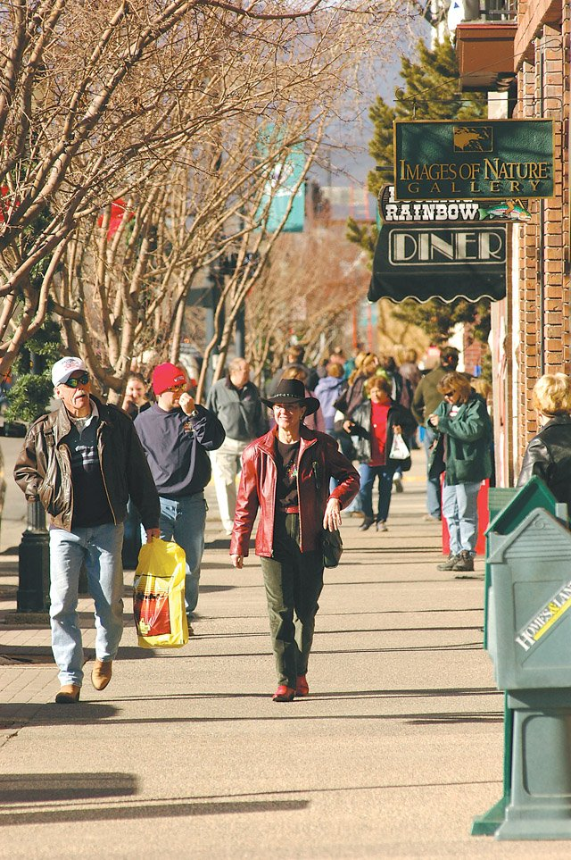 Shoppers pound the sidewalks, moving from store, to store during a big shopping day in November.