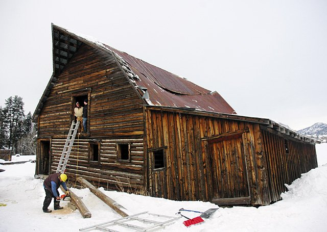 Fred Hughes uses a chainsaw to cut timber Monday. The wood was used to help shore up the More Barn, which has developed into a landmark symbol in Steamboat Springs. A roof beam collapsed at the barn, and an effort is being made to stabilize it before it can undergo a $150,000 refurbishment later this year. Dana Carl of D.C. Enterprises looks out the loft door of the historic barn with Gunnar Hughes.