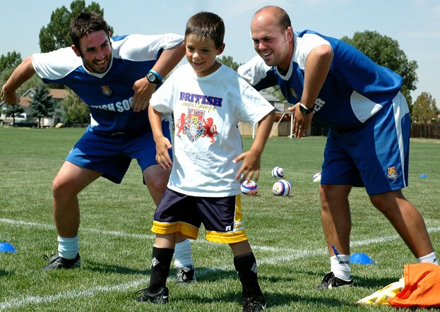 "Brent Cook, 7, dances with Challenger British Soccer Camp coaches Kenny McComish, left, and Danny Richardson during the awards ceremony, concluding the camp Friday at Woodbury Park in Craig. The coaches taught Cook the dance because the British television show ""The Office"" has a character named David Brent that does the dance."