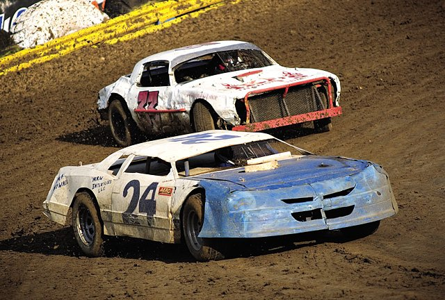 Richard Wisecup, in the blue and white car, and Jason Rettman, in the red and white car, race around the dirt track at the Hayden Speedway on Saturday night.  Wisecup&#39;s car blew a tire later in the race and had to be towed off the track.