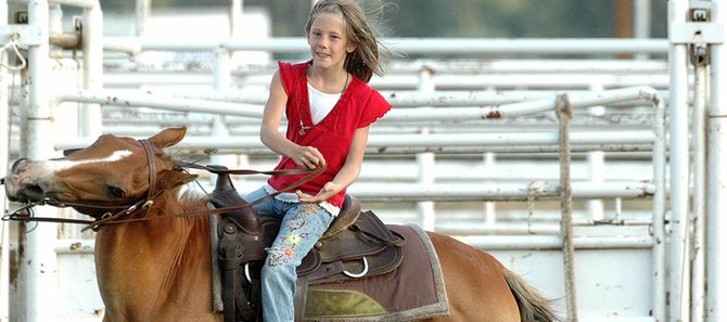 Karmen Christopher, 8, looks up as she controls her horse around a barrel in the barrel racing competition.