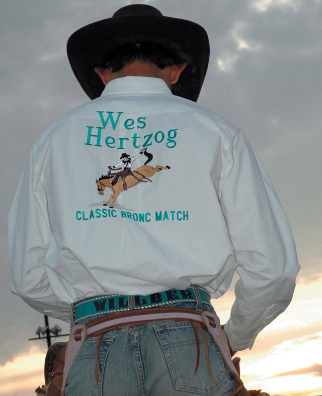 Bronc buster Will Berg looks over his saddle as the sun sets on the Moffat County Fairgrounds. Berg was wearing the shirt honoring Wes Hertzog that all of the competitors wore.