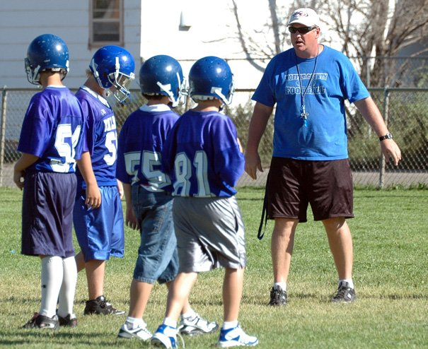 Craig Middle School football coach Todd Hildenbrand looks on as the Bulldogs work on offensive drills at Monday's practice, two days after CMS defeated Steamboat Springs, 42-6.