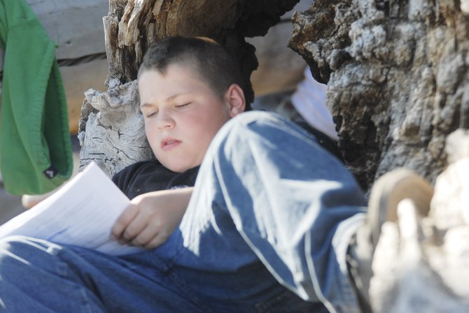 Dusty Knight, 10, fills out his journal about his trip while lounging in a tree just before dinner.  The journal is meant to keep track of the things the children have done, and will be used as a discussion tool in class.