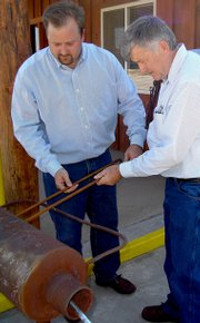 Brian and Clarence Elkin of the Summit National Bank in Baggs, Wyo., heat up branding irons in preparation of burning local ranch brands into the front of the bank on Wednesday afternoon. Clarence, bank president, has been an agricultural lender for 35 years and the family opened the Baggs branch five years ago.