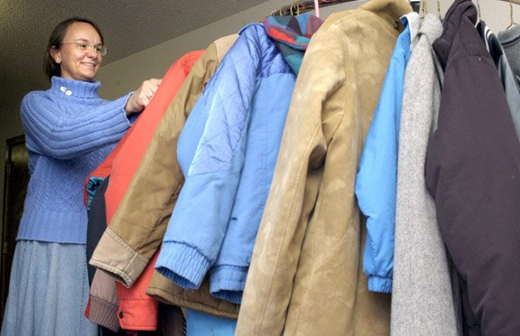 Pat Jones, director of Love INC, looks at a rack of coats available at the Community Coat Drive in 2005. The organization will again distribute coats to people in need, regardless of income.