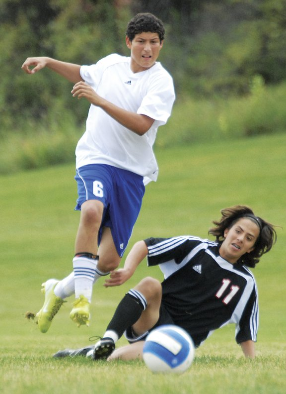 Armando Lopez of Moffat County drives past Gonzalo Gomez of Eagle Valley on his way to score the third point with eight minutes left in the game.  Moffat County won the game, 3-2.