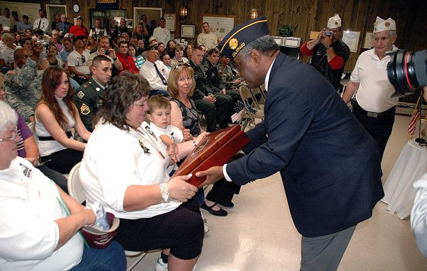 Sherri Lawton, widow of the late Staff Sgt. Mark A. Evans-Lawton, receives a wooden case for the American flag during an August 2006 ceremony honoring her husband and renaming the Craig American Legion Post after him. Sherri Lawton, a former Hayden resident, is asking the community to contact their state lawmakers in hopes of stopping a Flagstaff, Ariz., distributor from selling anti-war T-shirts decorated with the names of fallen Iraq veterans.