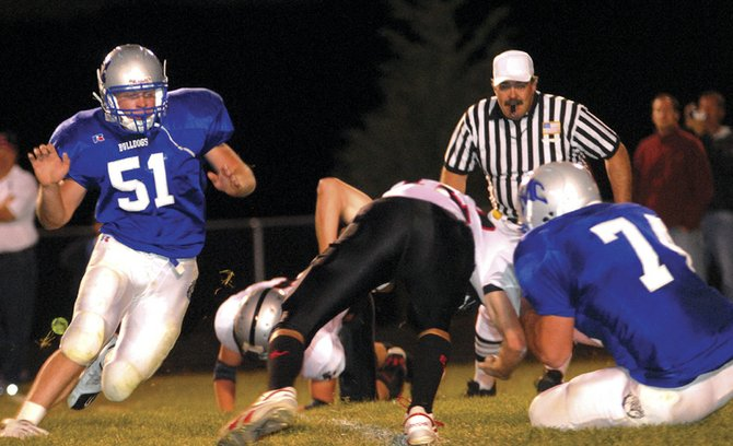 Robert Daniels, left, and Travis Wilson of Moffat County sack Hunter Blevins of Eagle Valley in the second quarter of the homecoming game Friday night. The final score was 20-6 in Eagle Valley's favor.