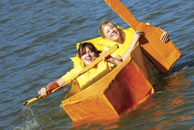 "Emily Norris, front, and Emily Hepworth ride in a boat titled ""Rubber Ducky"" at the Moffat County science department's Science Olympics Cardboard Regatta on Friday afternoon at Loudy-Simpson Park.  Teams built their boats out of cardboard only and were supplied a limited amount of duct tape to hold the boats together."