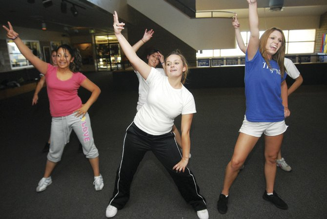 Karen Torres, Amanda Wilson and Makinzie Bretches of the Moffat County High School dance team practice in the second-floor common area Thursday evening.