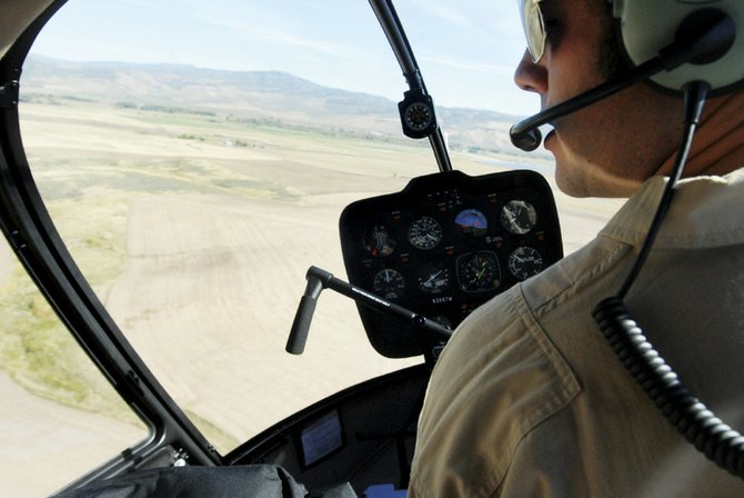 Drew Mitchell pilots a Robinson R44 Raven II over the Yampa Valley on his way to Craig from the Yampa Valley Regional Airport. Mitchell is an instructor for Colorado Northwestern Community College's new helicopter aviation program.