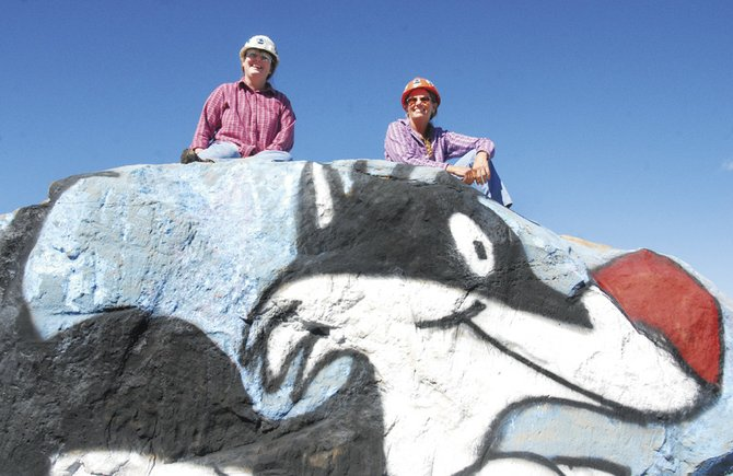 "Tonia Perkins, left, and Wanda Nickels sit atop their newest creation, ""Sylvester,"" Tuesday afternoon at Trapper Mine. The pair has created all sorts of paintings on large rocks placed by Trapper employees."