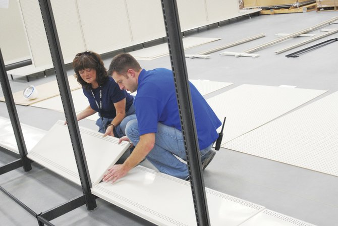 Maureen Ridnour, left, and John Howerton put together new shelving Tuesday afternoon at the Wal-Mart SuperCenter in Craig. The store is on scheduled to open Nov 7.
