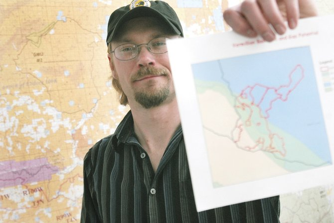 Jeremy Casterson, Bureau of Land Management planning and environmental coordinator for the Little Snake Field Office, holds up a map of the Vermillion Basin with colored sections indicating different natural gas potentials.  The northern part of the basin is a high-potential area, but there has not been a study to determine the amount of gas there.
