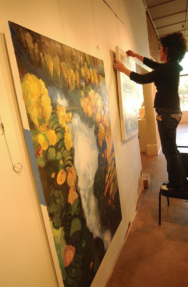 Painter Susan Schiesser hangs one of her paintings Monday at the Artists' Gallery of Steamboat.