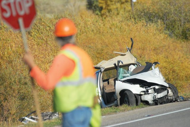 A construction worker directs traffic past one of two cars involved in a fatal crash that killed two people Thursday afternoon on U.S. Highway 40 just west of Hayden.