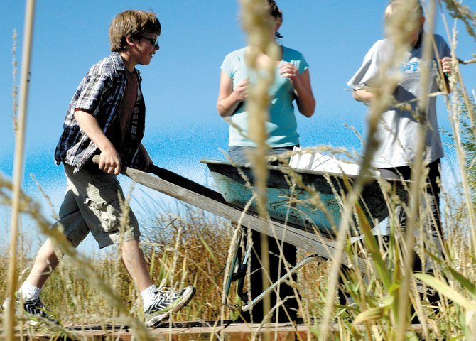 Trent Parrott wheels an empty wheelbarrow over a bridge past two classmates Wednesday morning at the Public Safety Center. Parrott and about 90 other Craig Middle School seventh-graders help lengthen the trail at the pond as part of a community service project.