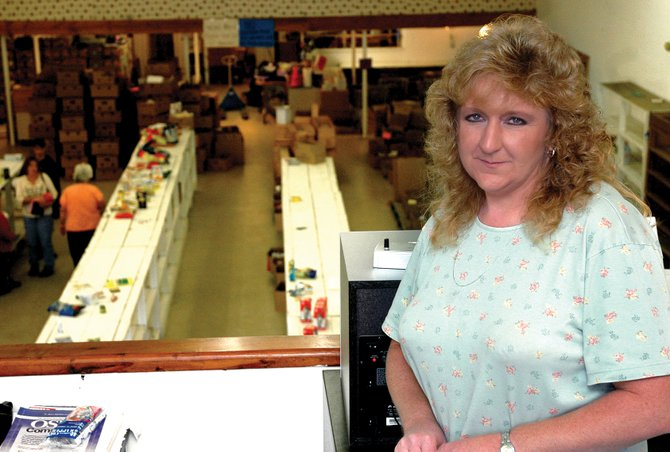 "Tina Williams managed Robb's Grocery Store in Craig for 14 years. The nearly empty shelves of the store below Williams are evidence of the liquidation that is going on as the building is in the process of being sold. Williams said, ""It's hard to leave something you've worked for, for a number of years. It's like my second home."""