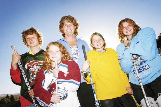 Shannon Samuelson with her children, from left, Michael, 13, Emma, 8, Lauren, 10, and Alex, 10, pose before heading to hockey practice Thursday evening at their home in Craig. Each of the children play multiple sports.