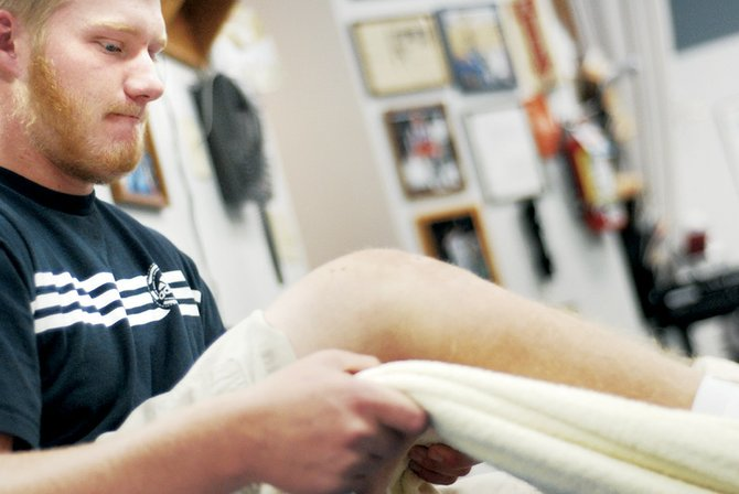 J.T. Haddan uses a towel to stretch his leg as part of rehabilitation training Wednesday afternoon after knee surgery Oct. 1. Haddan is on the Moffat County High School football team, but he was severely hurt early in the season and is training three times a week to repair the damage.