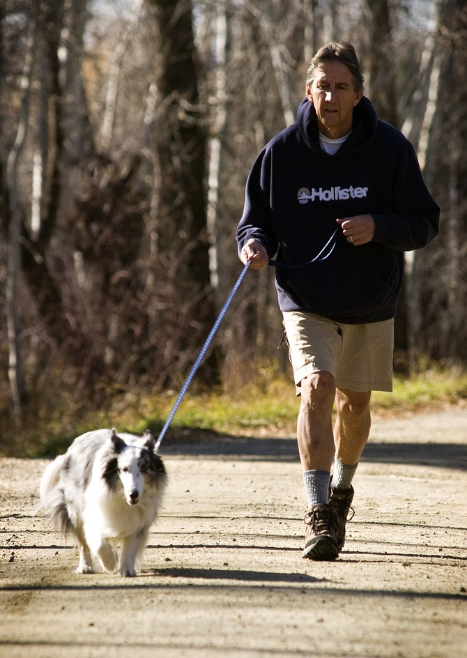 Bob Riley takes a walk with his dog, Madison, along the Spring Creek trail in Steamboat Springs on Tuesday afternoon. An off-leash trial program proposed by the Responsible Dog Ownership Group of Steamboat moved closer to fruition during a Steamboat Springs School Board meeting Monday night.