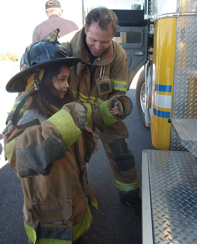 West Routt Fire Protection District firefighter Dal Leck helps Hayden Valley Elementary School first-grader Thalia Carbajal onto a fire engine Wednesday during a Fire Prevention Week activity.