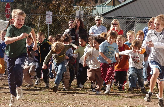 Soda Creek Elementary School fifth graders Danny LaPointe, far left, and Justin Miller, far right, lead a pack of first graders Thursday during the school's Pumpkin Fun Run. The event was organized by physical education teacher Chris Adams to promote fitness.