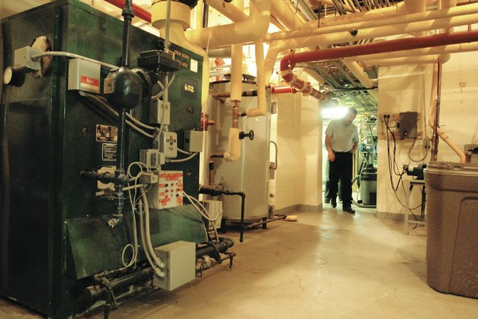 Vic Updike, facilities manager of The Memorial Hospital, walks through the boiler room, located under the hospital. The equipment was installed during the 1970s renovation, Updike said, and contains two boilers in case one needs repair.