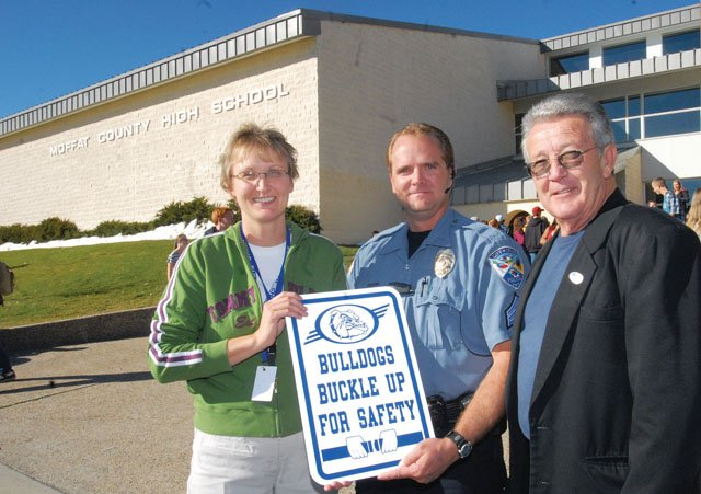 From left, Jane Harmon, Moffat County High School principal, Police Sgt. Dusty Schulze and Tony St. John pose Thursday afternoon in front of the high school with signs that encourage students to buckle up. The signs are part of a program, starting next Wednesday, that rewards drivers who buckle up.