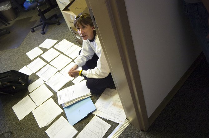Routt County Search and Rescue Treasurer Kristia Check-Hill sits in the organization's offices on  Yampa Street in Steamboat Springs on Friday afternoon surrounded entirely by bills and paperwork.