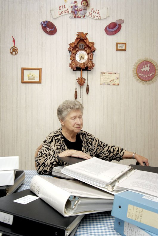 Phyllis Bingham sits in her home Saturday afternoon in Craig. She is surrounded by some of the 21 volumes of obituaries and newspaper articles she has compiled. The first article she transcribed dates back to 1876.